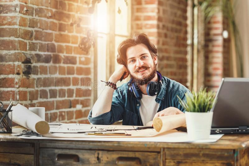 Красивый бородатый архитектор сидя на его столе стоковые фотографии rf