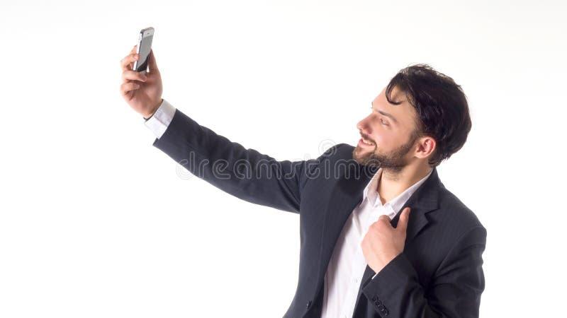 Красивый бородатый молодой бизнесмен принимая усмехаться selfie портрет изолированный над белой предпосылкой студии стоковое изображение