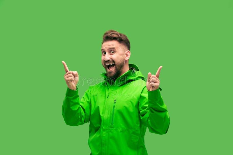 Красивый бородатый молодой человек смотря камеру изолированную на зеленом цвете стоковое изображение rf