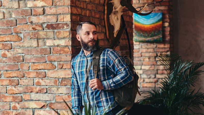 Красивый бородатый мужчина битника в голубой рубашке и джинсах ватки с склонностью рюкзака против кирпичной стены на студии стоковое фото rf
