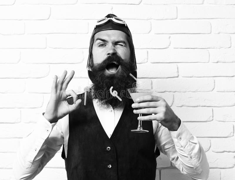 Красивый бородатый человек авиатора с длинной бородой и усик на смешной стороне держа стекло спиртного коктеиля в годе сбора вино стоковая фотография