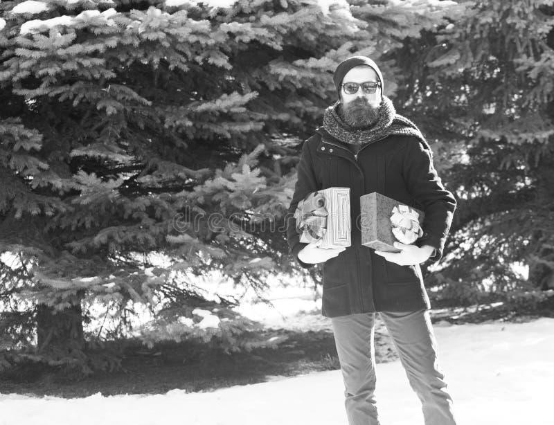 Красивый бородатый человек, битник, с бородой и усиком в черных солнечных очках, шляпе, пальто и шарфе с подарочными коробками ка стоковые фотографии rf