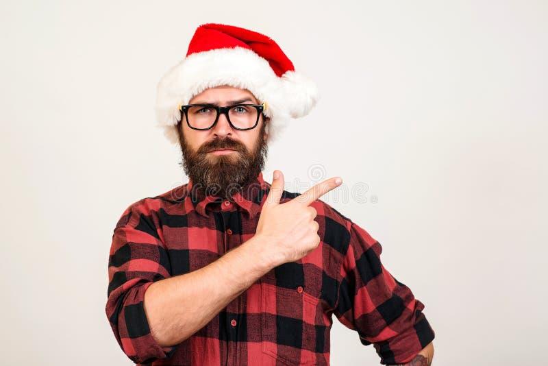 Красивый бородатый человек в шляпе и стеклах Санта Человек Санта указывая на сторону над белой стеной Принципиальная схема рождес стоковое фото