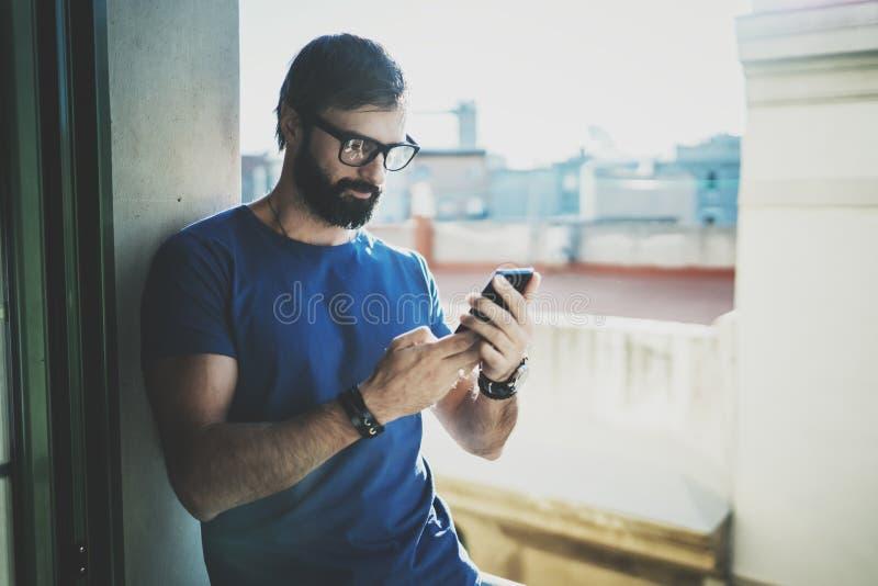 Красивый бородатый человек держа руки smartphone и касающий экран современного мобильного телефона запачканная предпосылка Blogge стоковая фотография rf