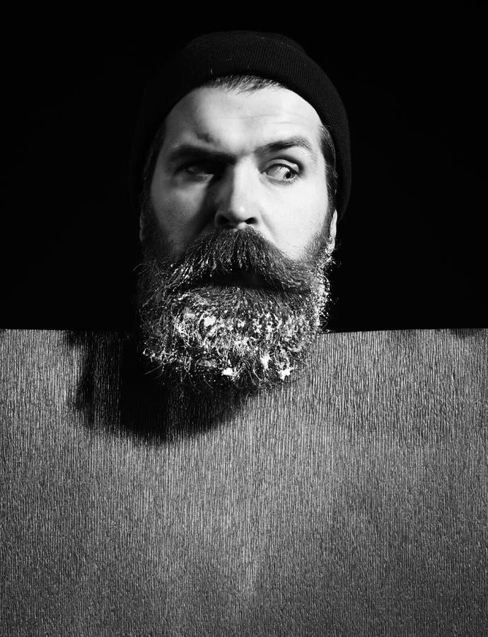 Красивый бородатый человек или парень в шляпе зимы с модным усиком на удивленной стороне и снег в бороде около красной бумаги стоковое фото rf