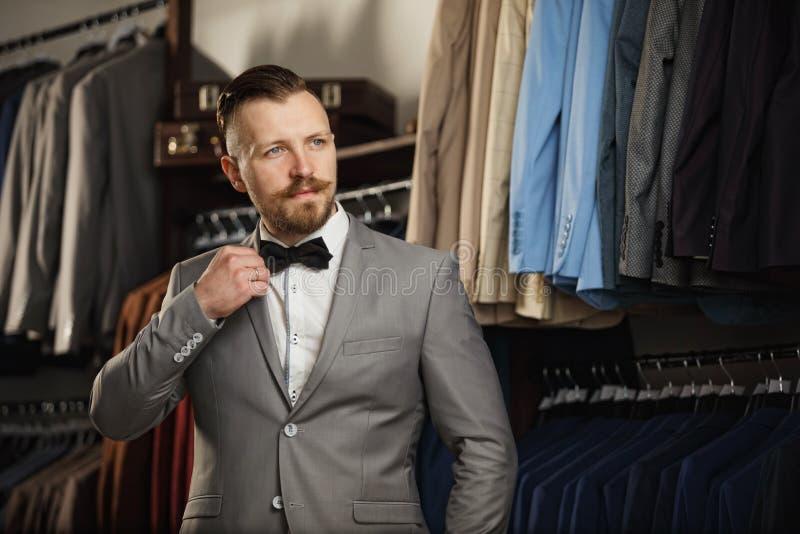 Красивый бородатый бизнесмен в классическом костюме Человек в классическом жилете против строки костюмов в магазине стоковые изображения