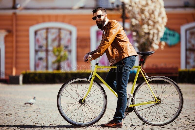 Красивый бородатый молодой человек в солнечных очках на велосипеде в городе Концепция велосипеда стоковое фото rf