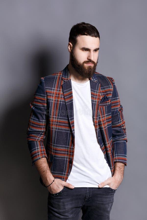 Красивый бородатый человек представляя с руками в карманн стоковое фото