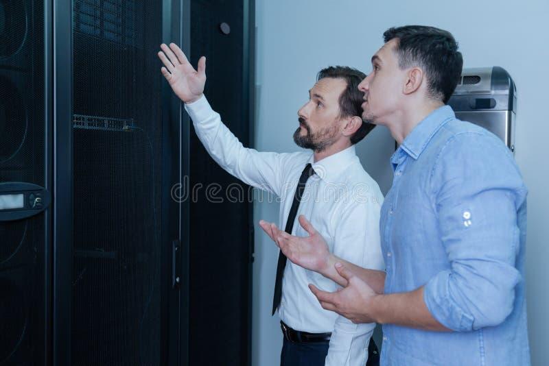 Красивый бородатый человек указывая на сервера данных стоковые фото