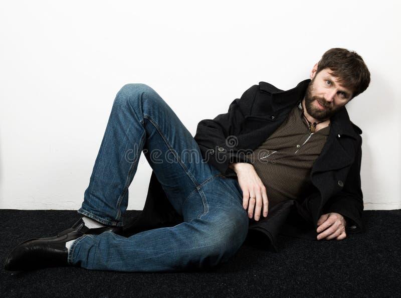 Красивый бородатый элегантный бизнесмен в куртке, джинсах и шерстяном представлять пальто концепция feshion стоковая фотография rf