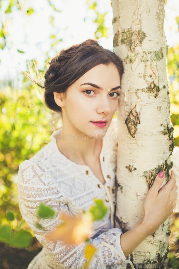 Красивый брюнет с оплетками вокруг головы в блузке рукава винтажного белого шнурка длинной под деревом березы стоковое фото rf