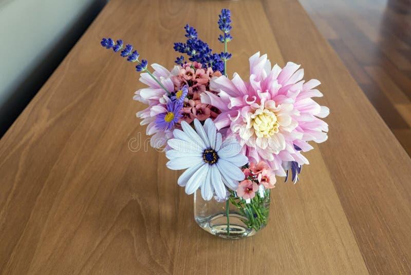 Красивый букет ассортимента ежегодников и постоянных цветков на таблице твердой древесины стоковая фотография