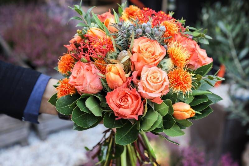Красивый букет в цветах коралла оранжевых роз, тюльпанов, multifida ятрофы, tinctorius Carthamus и других заводов в мужчине стоковые фотографии rf