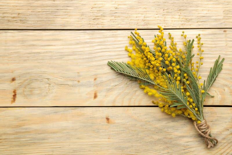 Красивый букет желтых цветков мимозы на естественном деревянном столе Взгляд сверху открытый космос Космос для текста стоковое изображение rf