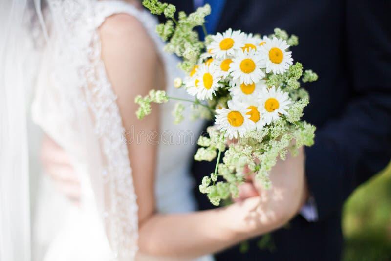 Красивый букет желтого стоцвета в руках жениха и невеста стоковая фотография rf