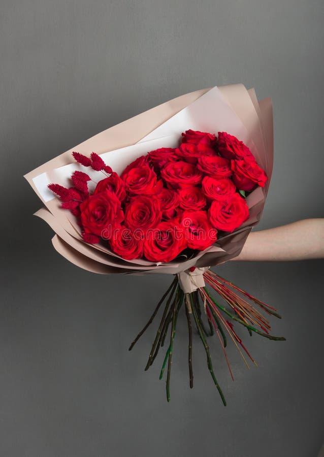 Красивый букет красных роз на серой предпосылке стены стоковая фотография
