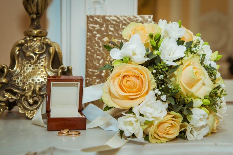 Красивый букет невесты с желтыми розами, белыми цветками и кольцами золота с коркой на день свадьбы стоковые фотографии rf