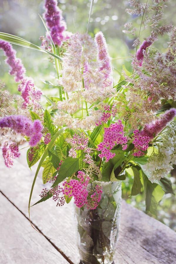 Красивый букет полевых цветков на деревянной поверхности в лучах заходящего солнца Лето, природа, красота вертикально стоковая фотография
