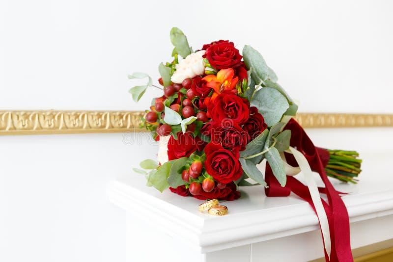 Красивый букет свадьбы красных роз и обручальных колец золота в белом интерьере стоковое фото