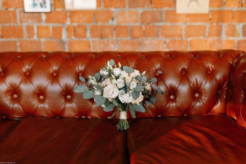 Красивый букет свадьбы помещенный на кожаной софе стоковые изображения