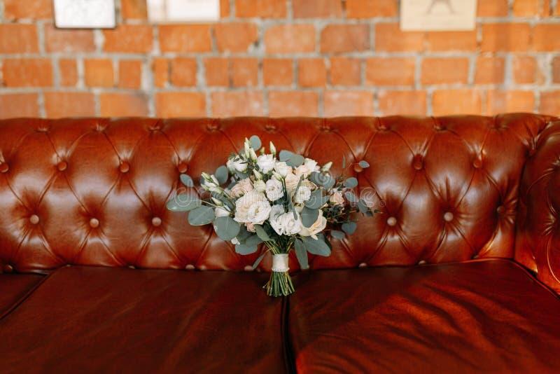 Красивый букет свадьбы помещенный на кожаной софе стоковые изображения rf