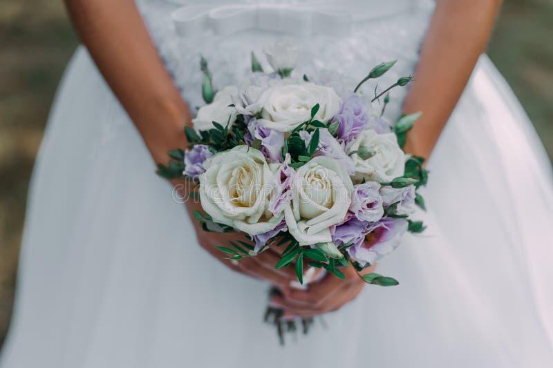 Красивый букет свадьбы в руках невесты Пион поднял, хлопок, розы Белизна и Vioolet Ультрамодные и современные цветки свадьбы стоковая фотография