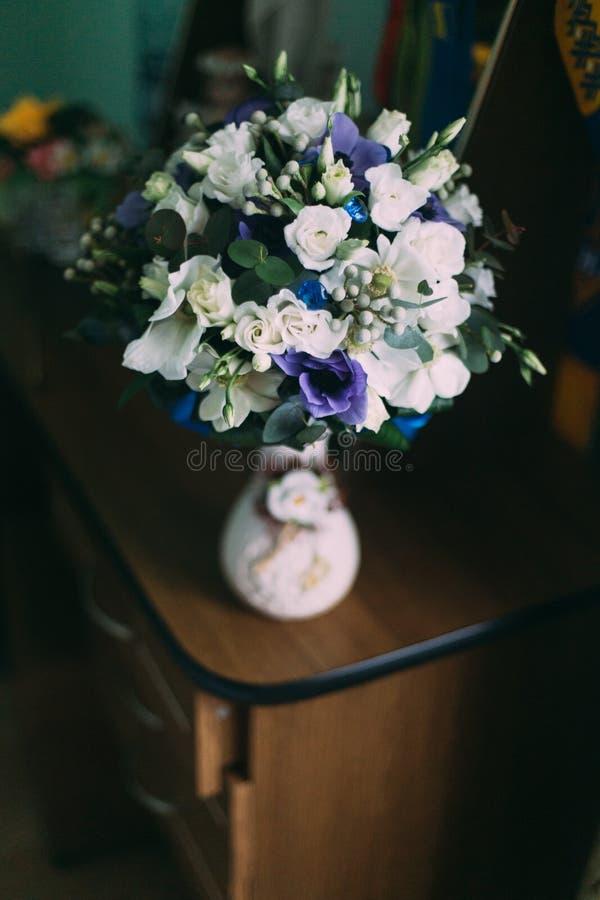 Красивый букет цветков весны фиолетовых и белых в вазе на деревянном столе стоковое фото