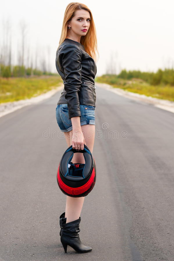 Красивый велосипедист женщины стоя на дороге с шлемом мотоцикла в руке стоковая фотография