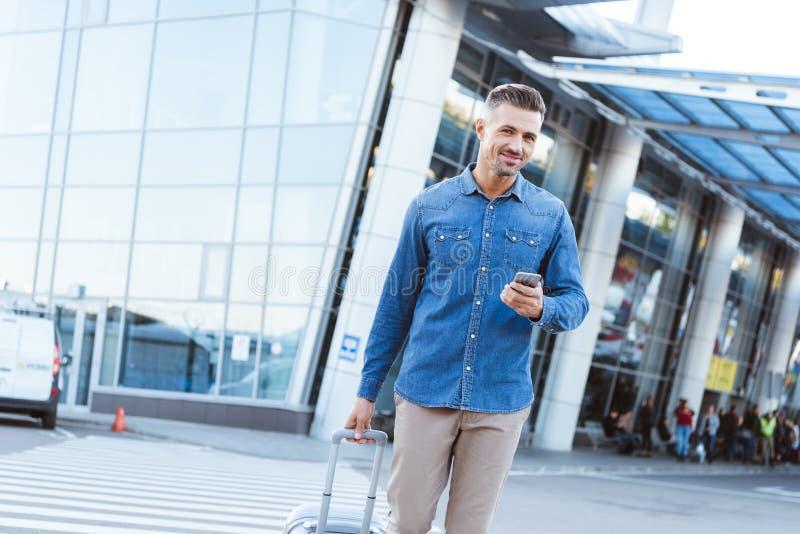 Красивый взрослый смартфон и усмехаться удерживания человека стоковые фотографии rf