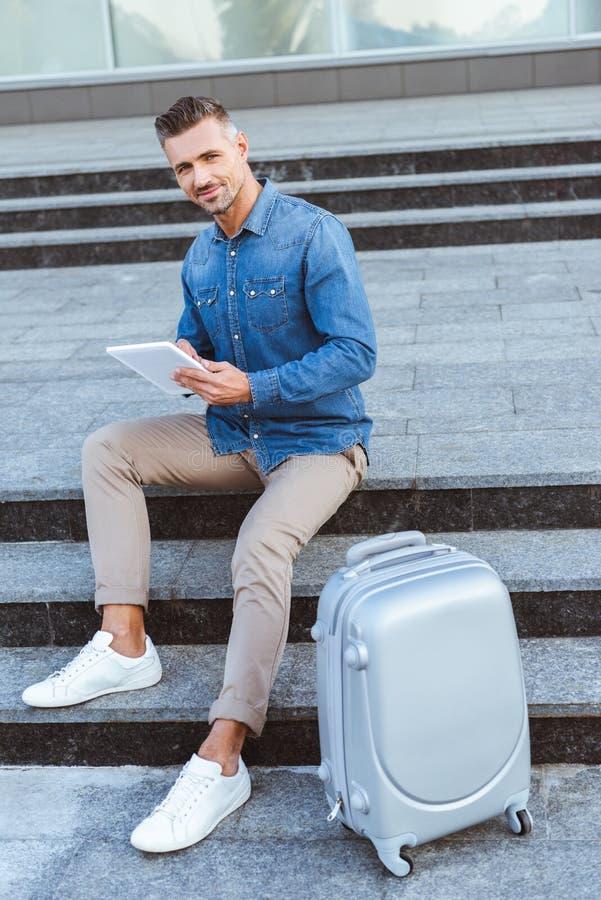 Красивый взрослый человек используя цифровой планшет и усмехаться на камере пока сидящ на лестнице стоковое изображение rf
