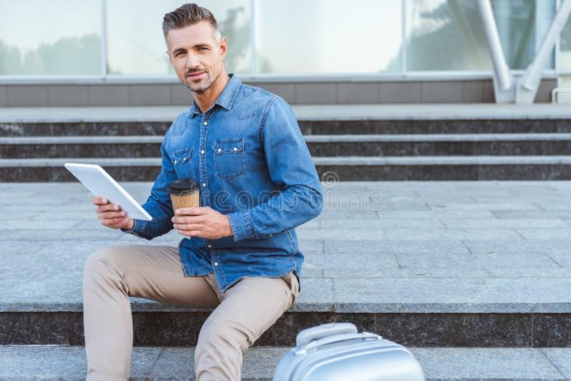 Красивый взрослый человек с кофейной чашкой сидя на лестнице, держащ цифровой планшет и усмехаться стоковое фото