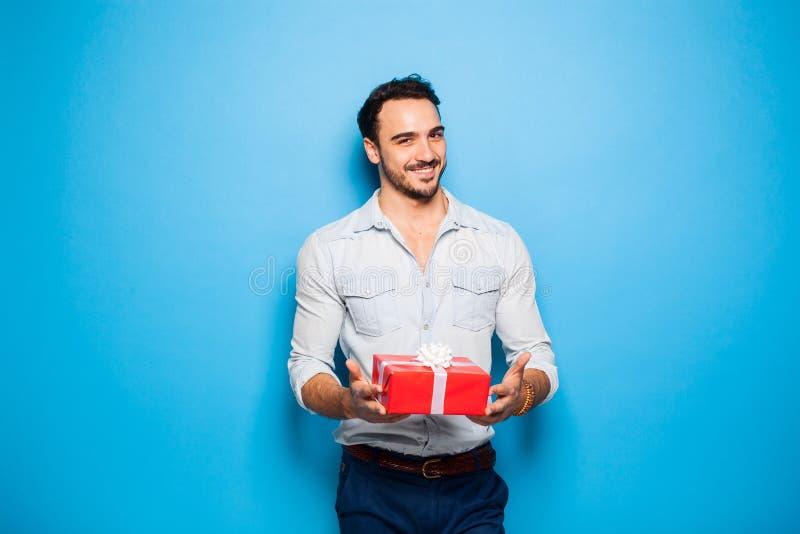 Красивый взрослый человек на голубой предпосылке с подарком рождества стоковое фото rf