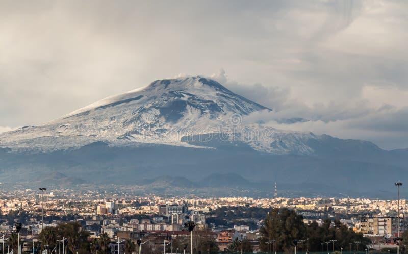 Красивый вид извержения вулкана Этна с дымом и снегом и городом Катании на фото в зиме в Сицилии стоковые изображения rf