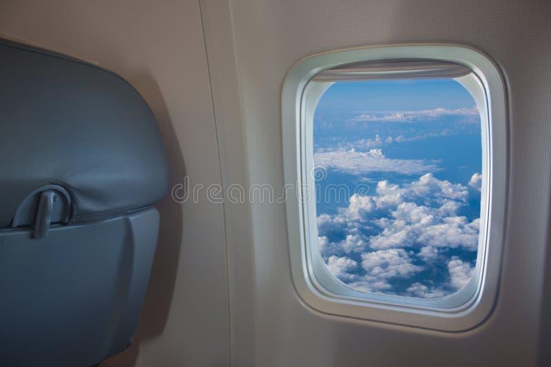 Красивый вид из окна самолета к голубому небу с белыми облаками на высоте в солнечном дне от сидения пассажира стоковое изображение rf