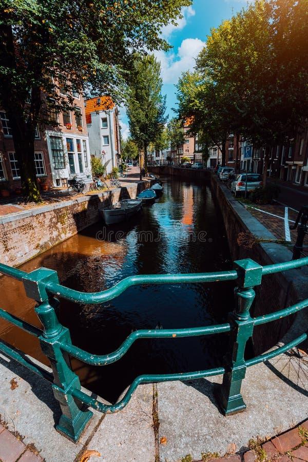 Красивый вид канала Амстердама с мостом и типичных голландских домов в теплом свете после полудня r стоковая фотография