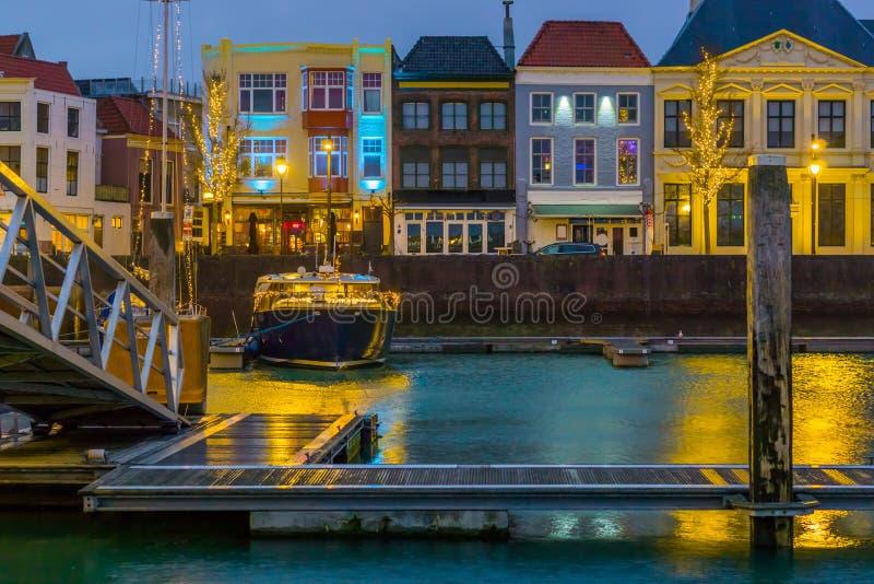 Красивый вид на городе vlissingen вечером от доков, освещенной шлюпки и зданий, популярного города Зеландии, стоковая фотография rf