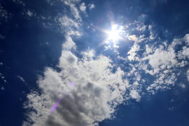 Красивый вид на солнечные лучи с некоторыми пирофакелами объектива и облака на голубом небе стоковые изображения rf