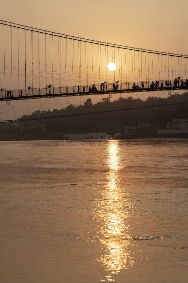 Красивый вид обваловки и моста Ганга на заходе солнца Rishikesh, Индия стоковая фотография