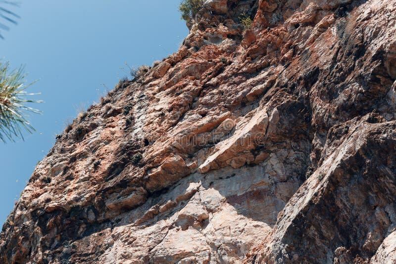 Красивый вид скалы против голубого неба, нижний взгляд Камень текстуры естественный стоковые изображения