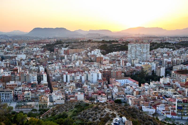 Красивый вид старого городка и держатель Benacantil от Санта-Барбара рокируют наслаждаться заходом солнца Alicante, Испания стоковые фото