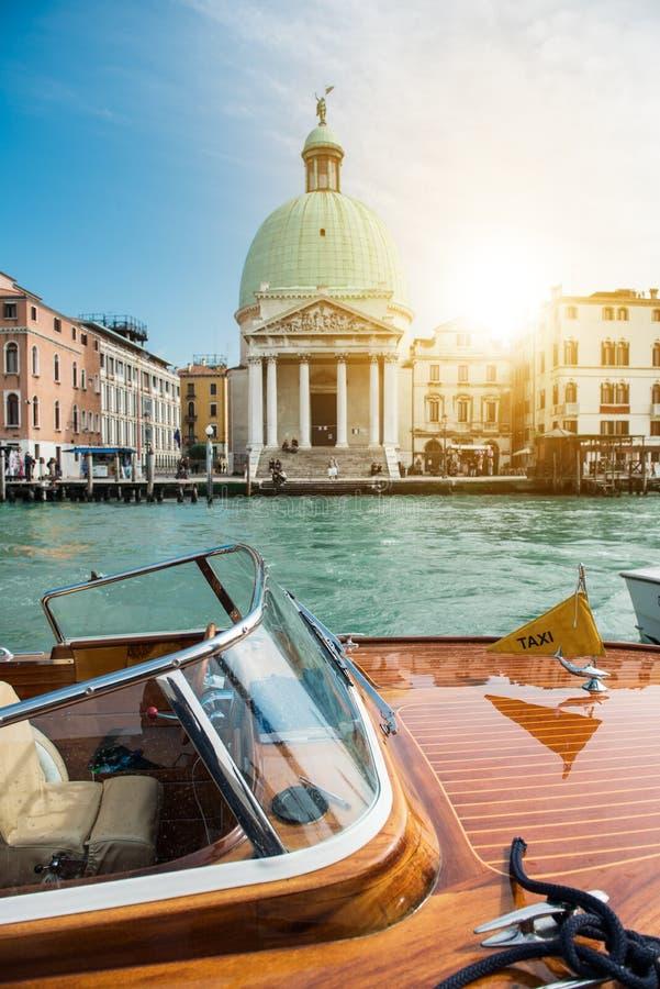 Красивый вид традиционной шлюпки такси на известном канале большом с базиликой в золотом свете захода солнца в Венеции, Италии стоковая фотография