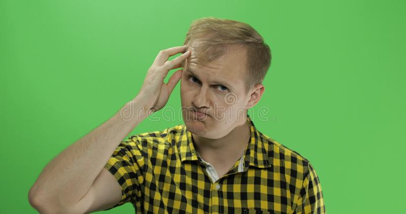 Красивый внимательный человек в желтой рубашке смотря в камере и думает стоковые изображения