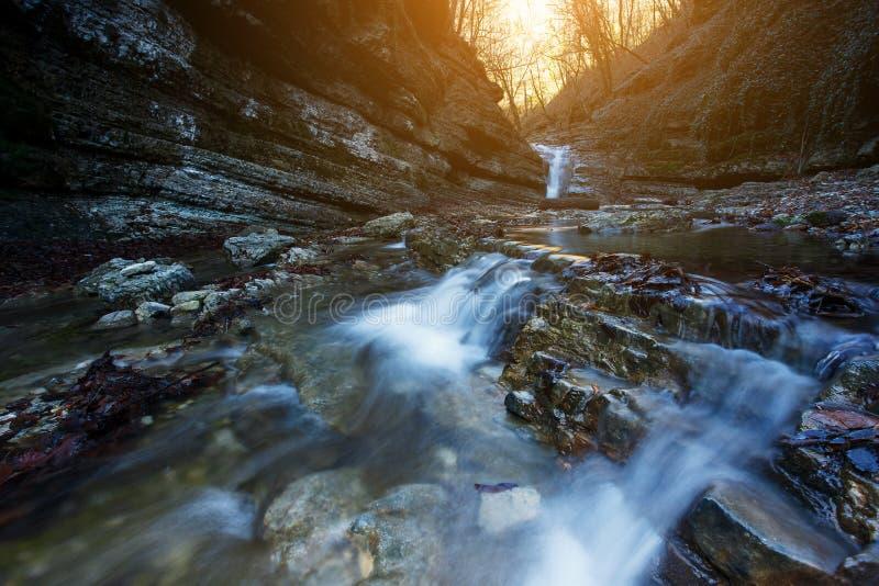 Красивый водопад на реке горы в красочном лесе осени с красным цветом и апельсином выходит на заход солнца яблоко заволакивает ва стоковые фото
