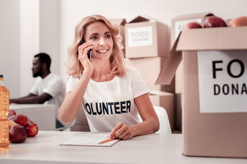 Красивый волонтер имея важный звонок стоковое изображение