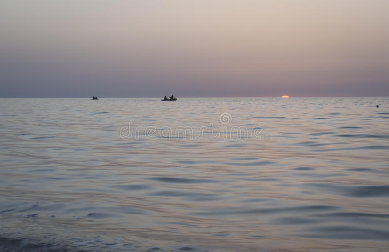 Красивый восход солнца над морем, рыболовами в шлюпке стоковое изображение