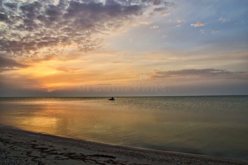 Красивый восход солнца на побережье и человеке в шлюпке стоковое фото rf