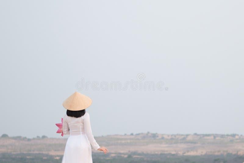 Красивый вьетнамец держа розовый лотос в белой песчанной дюне стоковое фото