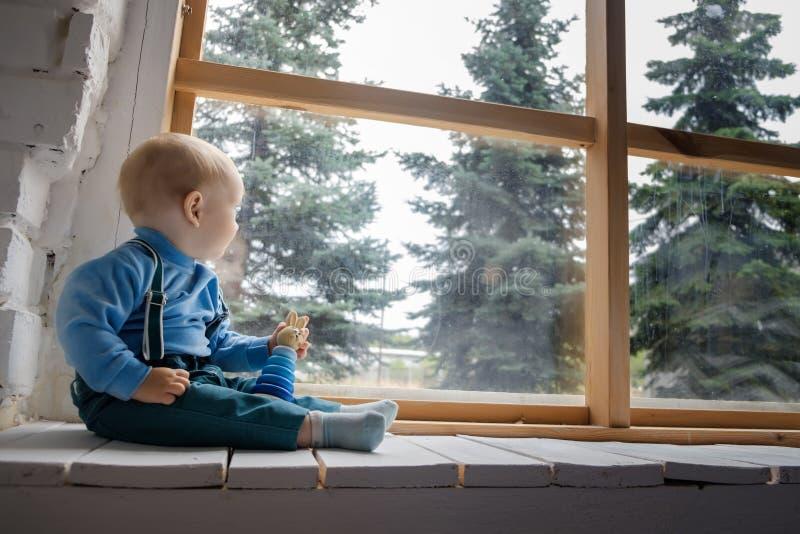 Красивый голубоглазый младенец сидя на windowsill и взглядах вне окно на зеленых деревьях стоковая фотография rf