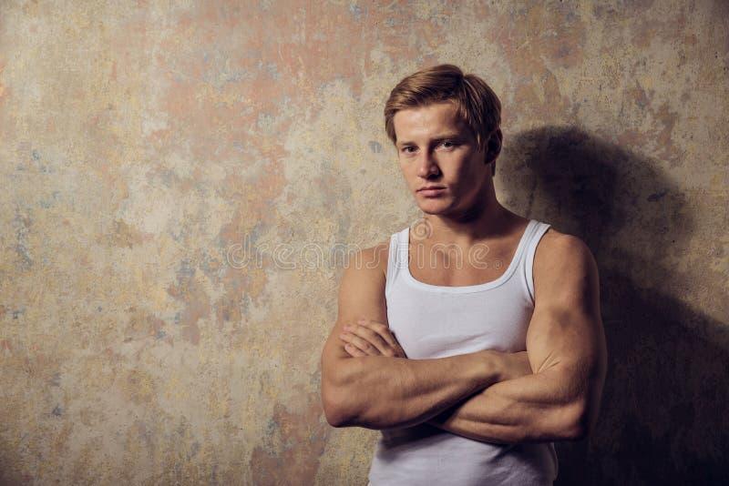 Красивый гомосексуалист в белой футболке представляя против предпосылки grunge стоковое изображение