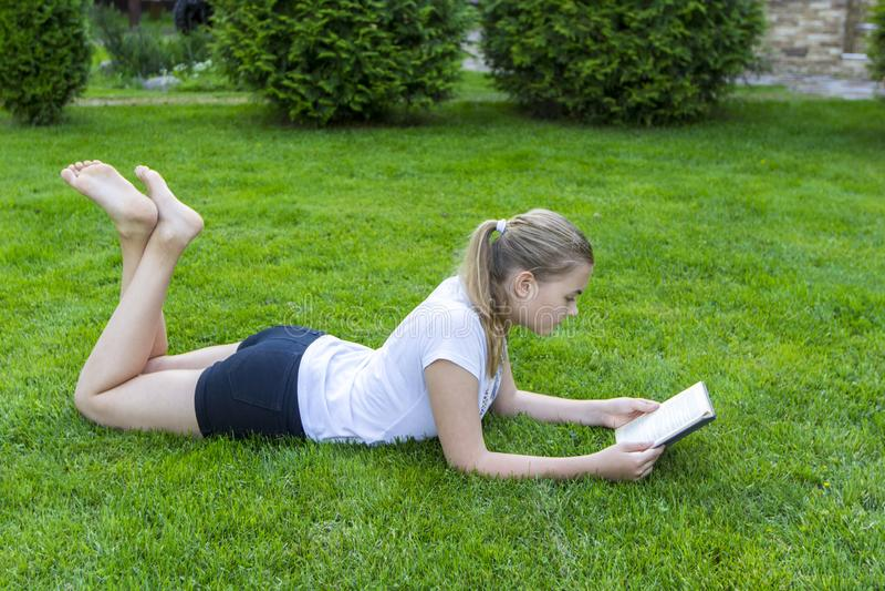 Красивый девочка-подросток лежит на зеленой траве и читает книгу в парке на день лета солнечный стоковые фото